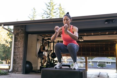woman doing box jumps as part of a CrossFit workout in her driveway