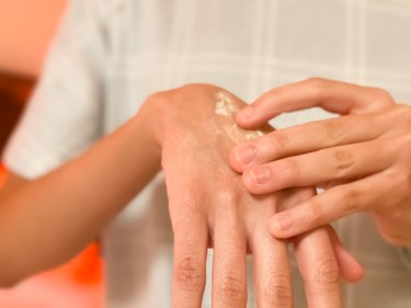 mixed-race young female lotions her dry hands before bed