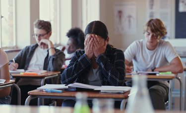 Crying female student struggling with schoolwork in a classroom.