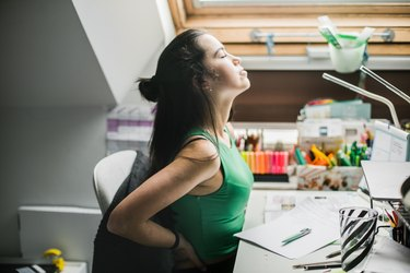 Young woman having back pain while sitting at desk