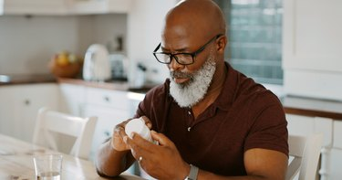 Older man with beard in kitchen looking at vitamin container