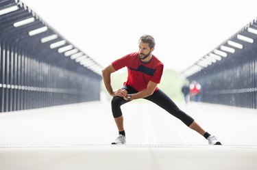 Man in a red shirt doing a side lunge leg exercise on a bridge