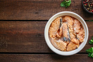 canned salmon, fish preserves (seafood in a tin can) menu concept background. top view. copy space