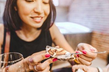 Woman eating a zinc-rich oyster, close-up at a restaurant