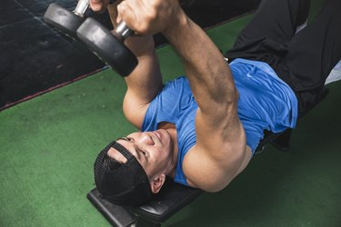 closeup of a fit Asian man in a blue shirt and hat doing the dumbbell skull crushers exercise on an exercise bench