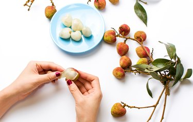 Female hands peeling lychee fruit