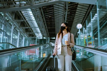 Asian businesswoman traveler with face mask on the move using escalator in airport.