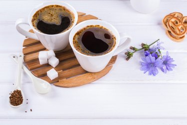 Cup of coffee tea chicory drink hot beverage  with chicory flower and sugar cookies. Still life with breakfast