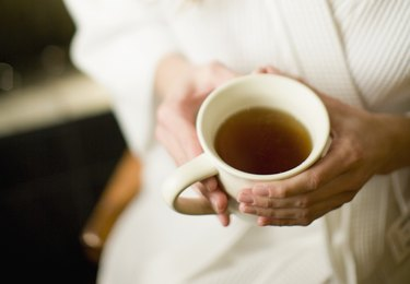 Woman holding cup of peppermint tea for gas pain relief
