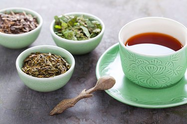 A cup of tea next to dried tea leaves