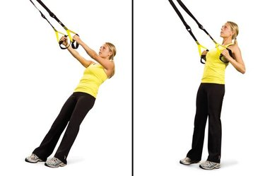 Woman performing low row TRX exercise