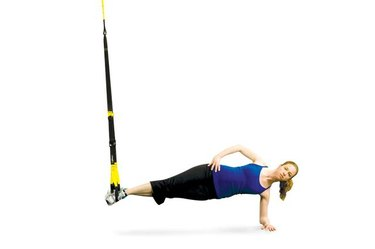 Woman performing TRX side plank.
