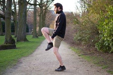 Man performing high knees before a bike ride
