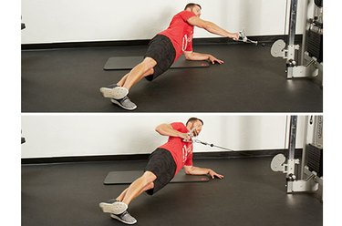 Man performing side-plank cable row on the cable machine