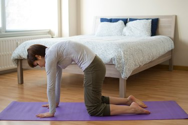 Woman demonstrating how to do Cat-Cow yoga pose for sleep