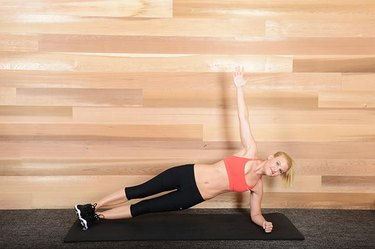 Woman performing side plank ab exercise.