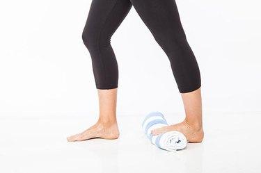 Woman demonstrating gastroc calf stretch.
