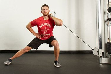 Man performing cable lateral lunge on the cable machine