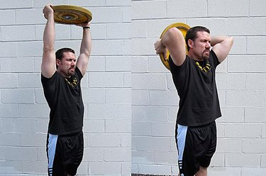 Man performing plate tricep press.
