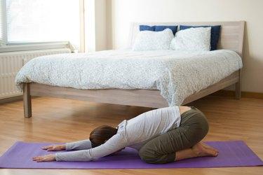 Woman demonstrating how to do Child's pose yoga for sleep