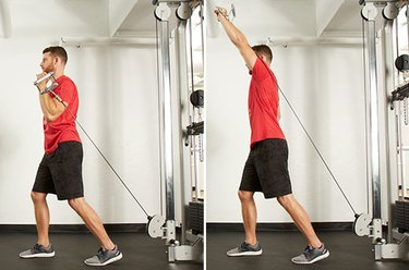 Man performing split-stance single-arm shoulder press  on the cable machine
