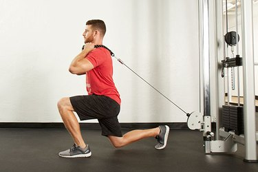 Man performing cable reverse lunge on the cable machine