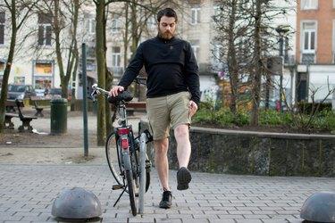 Man performing leg swing before a bike ride