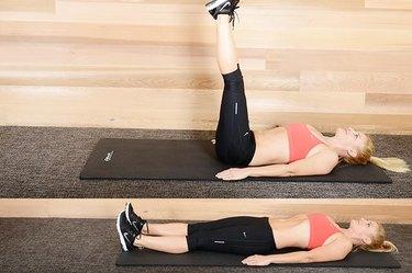 Woman performing straight leg raises ab exercise.