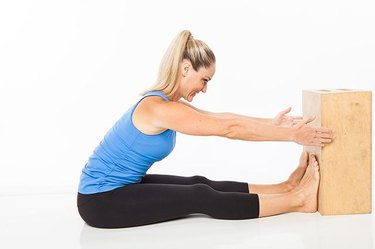 Woman demonstrating forward bend.