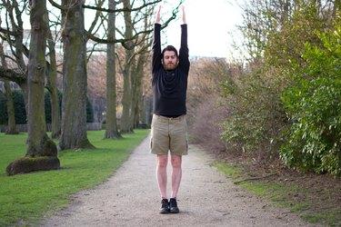Man performing shoulder reach before a bike ride