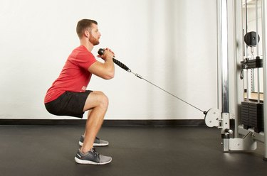 Man performing cable front squat on the cable machine