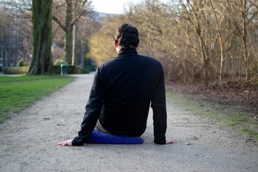Man foam rolling muscles on ground before a bike ride