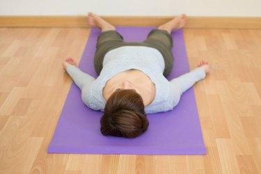 Woman demonstrating how to do Corpse pose yoga for sleep