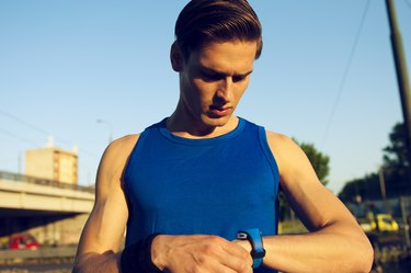 Handsome athlete checking pulse