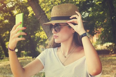 A young woman taking a selfie with her smartphone outdoors