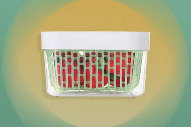 White container with green basket insert containing strawberries over yellow and green background.
