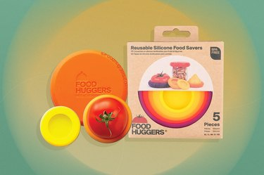 Food huggers silicone round food savers in yellow and orange over yellow and green background.