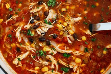 Bowl of shredded chicken tortilla soup with black beans corn and tomato sauce.