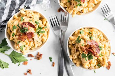 Bowl of macaroni an cheese with bacon pieces and herbs over gray background.