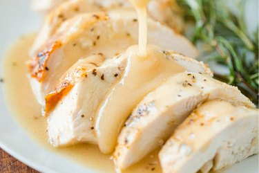 Sliced chicken breast topped with gravy on a white plate.