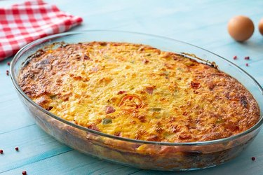 High Protein Easy Denver Omelet Hash Brown Casserole in a clear casserole dish with a red gingham napkin