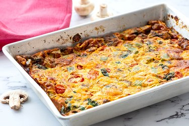 High Protein Breakfast Casserole Loaded Vegetable Egg Bake in a white casserole pan with mushrooms