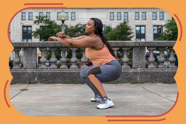woman in orange tank top and leggings doing a squat burpee modification with arms extended outside on balcony