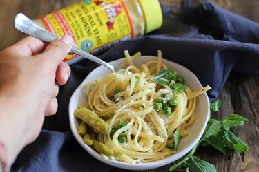 bowl of spaghetti with peas with Bragg nutritional yeast on the side
