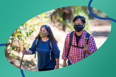 couple in face masks hiking outside to take more steps for the daily steps challenge
