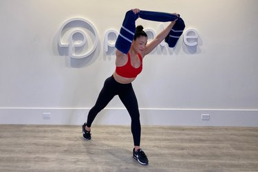 Woman doing a towel workout for back in a fitness studio