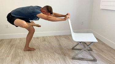 Man doing a standing figure 4 stretch with an office chair