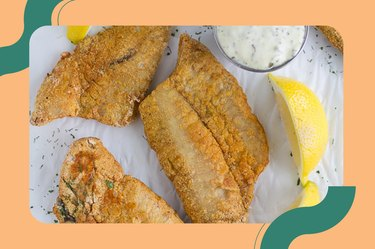 Crispy Air Fryer Fish with lemon wedges and a white dipping sauce