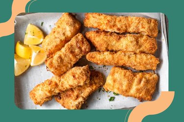 Air Fryer Fish & Chips on a white plate with French fries, lemon wedges and a white dipping sauce