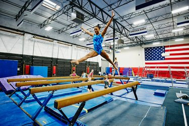 gymnast practicing balance beam wearing blue leotard in front of american flag